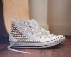 white converse high-tops with gold studs.