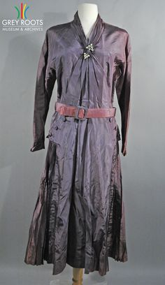 A purple, long-sleeved, taffeta dress with a rhinestone pin at the centre collar. The dress also feautures a considerable amount of accordian pleating in the skirt. Grey Roots Museum & Archives Collection.