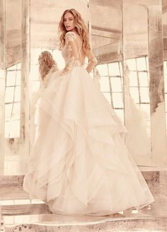 <p>Elysia</p>Ivory long sleeve lace bridal ball gown, V-front bateau illusion neckline, keyhole back with piping accent, cascading tulle skirt with thin double horsehair edging. Bridal Gowns, Wedding Dresses by Hayley Paige Bridal - JLM Couture - Bridal Style HP6556 by JLM Couture, Inc.: