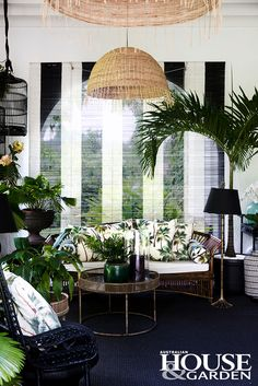 Palms, orchids and philodendrons flank the furniture in this corner. The cushions are made up in Hawaiian barkcloth for this living room in Singapore.