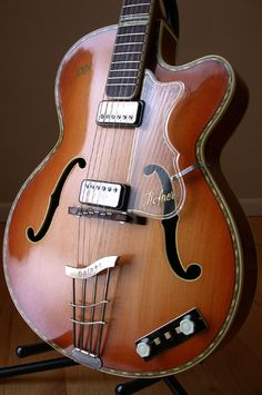 "Hofner 463 (1961). This mahogany bodied German archtop model 463 with ornate purfling was introduced in 1951. It has a solid spruce top, one piece ribbon mahogany back and ribbon maohgany sides. The body size is 16"", the neck is five piece (maple, mahogany, maple, mahogany, maple), and it has a 25.5 scale length. Note the ebony, height-adjustable, compensated bridge with adjustable fret-wire inserts, the Hofner Logo gold decal on upper bass bout, and the clear pickguard."