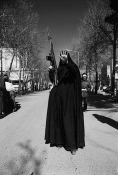 Kaveh Kazemi, Untitled. A woman, in black chador and carrying a G-3 machine gun, holds up her hand in a gesture of defiance to the camera. She is among the revolutionary forces occupying Tehran University a day after the victory of Islamic Revolution in Iran led by Ayatollah Ruhollah Khomeini. Tehran, February 12, 1979. Courtesy of the artist.