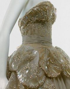 """Venus"" evening gown, by the House of Dior, ca. fall/winter 1949–50. From the Metropolitan Museum of Art: ""This extraordinary ball gown by Christian Dior, of foggy gray silk tulle, arrayed with an overlay of scallop-shaped petals, is called ""Venus."" The bodice and shell forms of its skirt are embellished with nacreous paillettes and sequins, iridescent seed beads, aurora-borealis crystals, and pearls. The glittering overskirt and train adumbrate both the seashell motif and the crescent wave…"