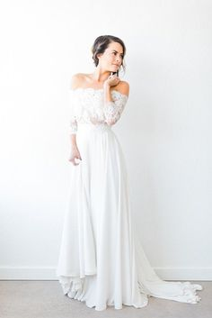 This off the shoulder fall wedding gown has long sleeves but still manages to slip us a better view of the bride's shoulders. Wonderfully romantic and feminine, it's a stellar style that'll make you feel like the prettiest of brides.                                                                                                                                                                                 More