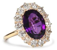 This oval cut amethyst estimated at 3.75 carats in weight is of fine gem quality, natural amethyst of great clarity and depth of color. The purple gem is embraced by thirteen (13) old European cut diamonds of an estimated 1.56 carats. (price: 4365.)