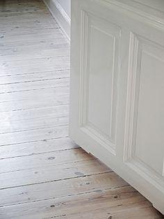 Whitewashing old wood floors in rehab design.