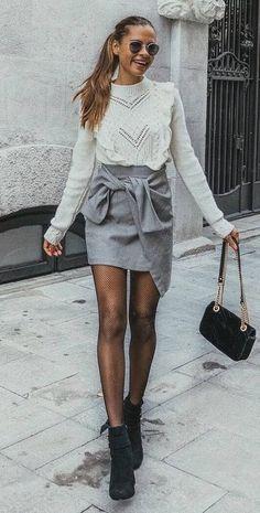 Pretty ruffled sweater with cute gray draped mini skirt.