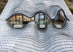 "GilBartolomé Architects creates cavernous ""Gaudiesque"" residence with a zinc-shingled roof."