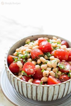 White bean and cherry tomato salad with a dressing of rosemary infused olive oil, garlic, Parmesan, anchovies, and lemon. So EASY! On http://SimplyRecipes.com
