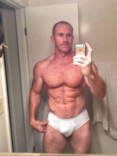 Ripped muscle hunk does a shirtless mirror selfie in packed white briefs