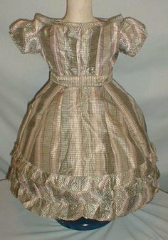 Child's 1860 era dress - A sweet child's 1860 mauve, white and gray plaid silk dress. The bodice has short puffed sleeve and a round neckline. The neck, armscyes and waist are piped. The skirt hemline is trimmed with ruffles. The dress is fully lined with cotton. The bodice has a back hook and eye closure.