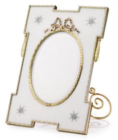 A Fabergé gold-mounted silver and guilloché enamel photograph frame, Moscow, 1899-1908, of house form, enameled translucent white over a guilloché ground, the four corners painted with bouquets en grisaille, the border with a dot and dash pattern, the bezel with varicolor gold ribbon-tied laurel wreath and surmounted by a red gold bow, the front hung with two varicolor gold swags of laurel. Formerly property of Millicent Rogers.