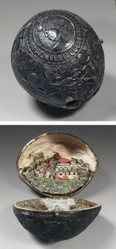 NOIX DE COCO sculptée d'un portrait entouré de fleurs et rinceaux feuillagés. Elle ouvre en deux parties découvrant une vue de Cayenne en relief. Milieu du XIXe
