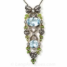 Enchanting late-Victorian/early-Edwardian jewel,  two and three-eighths inches long, dating from the turn-of-the-twentieth-century, glistens and glows with a featured pair of pastel blue aquamarines,  crowned with a diamond bow, garlanded in small lime demantoid garnets, and glittering with tiny old mine and rose-cut diamonds. Elegantly handcrafted in three hinged sections in darkened silver over rosy gold.
