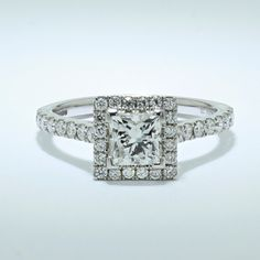 Classic design with a modern twist. Platinum princess cut halo engagement ring with diamond set shoulders