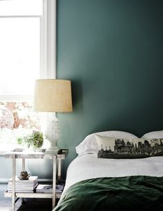 This forest green bedroom plays perfectly with the balance of colour and white. The green throw nods to the statement wall, while subtlety is kept through wooden textures and white bedding. Image: Livingetc