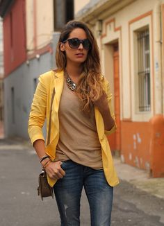 Yellow blazer paired with jeans, a beige top, and a lovely statement necklace