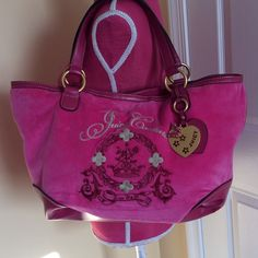 Juicy Couture bag NWOT Large Juicy Couture bag. Never used. Pink with tan detail. Gold hanging heart with pink butterfly and flower detail. Tan and pink interior with gold zipper pocket and gold pockets for lipstick and cell phone. Magnetic closure. Beautiful! Juicy Couture Bags