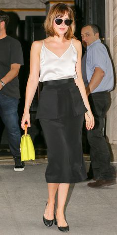 Dakota Johnson upped her street-style game when she hit the N.Y.C. pavement in a silky ivory cami and a black midi-length pencil skirt, both by Protagonist, with a chartreuse top-handle purse and black scalloped block heels.