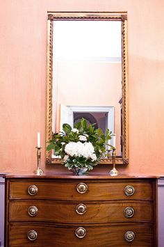 pale coral walls, tall mirror, vintage furniture, flowers
