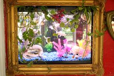 I seriously have to try this! Cut a 'window' in the wall and hang a frame over the fishtank!  Brilliant.  KATWISE