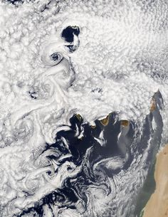 A vortex street often occurs when cloud formations over the ocean are disturbed by wind passing over land or another obstacle. In this true-color Moderate Resolution Imaging Spectroradiometer (MODIS) image from July 5, 2002, marine stratocumulus clouds have arranged themselves in rows, or streets, which are usually parallel to the direction of wind flow. Downwind of obstacles, in this case, the Canary Islands off the west African coast, eddies create turbulent patterns called vortex streets.