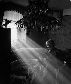 circa 1938: An old Czech woman sits in a shaft of light from a window, overhead hangs a decorated Christmas tree. (Photo by Hulton Archive/Getty Images)
