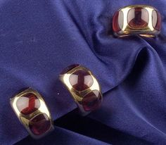 18kt Gold and Garnet Earclips and Ring, each bezel-set with three buff-top garnets, lg. 1 in., size 5 3/4.  Estimate $500-700