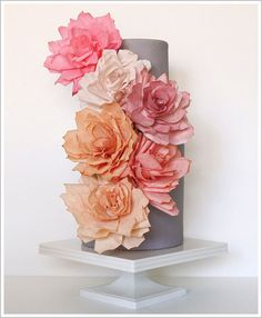 small gray cake with large paper roses covering the front.. all the roses are in the orange, peach, pink color ranges.