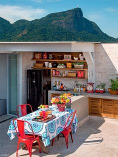Estas cadeiras vermelhas são o clássico modelo Tolix (Velha Bahia). Objetos do LZ Studio. Acima da bancada, prateleiras de madeira de demolição (Francisco Rodrigues Antiguidades).