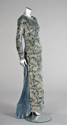the soft blue velvet ground stenciled in gold with Medieval style patterns, the sides inset with pleated silk and laced with silk cords and fastened w/ Murano beads