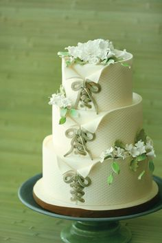 Three-tier toasted almond wedding cake covered with layers of delicately laced ivory fondant depicting a romantic corset accented with elegant handcrafted flowers at Sucré.