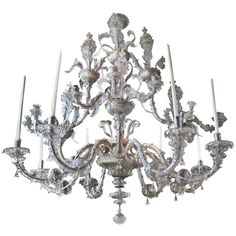 Massive 18th Century Venetian Chandelier Owned by Henry Ford, II  Venice, Italy  Circa 1750-80  Period 18th Century Clear Glass Venetian Chandelier. Handblown Murano Island Venetian Glass Supported by Hand Hammered Silvered Iron Frame. 24 arms. Baroque Work with Three Tiers of Poppies. The top most tier, realistically styled poppies in vases. The middle tier the poppies become the candle holders still realistically formed.