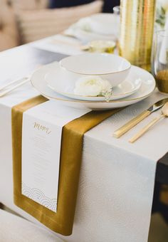 A gold and white place-setting at a vintage-inspired wedding.