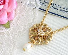 Gold Flower Filigree Necklace With Champagne Crystal And Pearls - Elegant Jewelry - Romantic Jewelry - Rhinestone Jewelry  Francis - is all about Gleaming and romance from the past for your Wedding day.  It is made 24k gold plated brass and combine with champagne Swarovski crystals and crystal pearls.  A very delicate crystal pearl was swings romantically from the bottom of the pendant.  Since the necklace is pretty short, it will work perfectly with an open neck  dress. $52