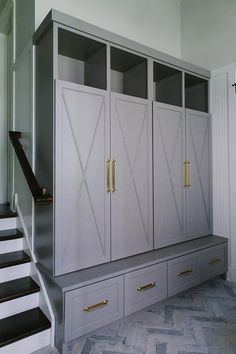 Gorgeous gray sunken mudroom boasts a gray herringbone floor leading to gray x-front close locker doors accented with brass handles and positioned below overhead shelves and above a gray storage bench. Mud Room Garage, Mudroom Laundry Room, Mud Room Lockers, Garage Lockers, Mudroom Cabinets, Garage Storage Cabinets, Diy Cabinets, Garage Makeover, Up House