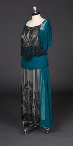 """Evening Gown: ca. 1919-1920, net, attached silk charmeuse slip, seed beads arranged in scrolling acanthus leaf pattern, sash, and a secret """"bust improver."""""""