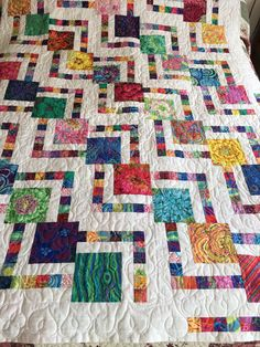 I saw a photo of this quilt and copied it. Mine is made with Kaffe Fassett prints and Kona Snow. It is basically a Log Cabin block made with the large