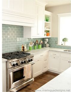 Beautiful kitchen! White to ceiling cabinets, blue/gray subway tiles, dark floors.
