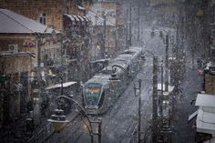 Israel Forever Jerusalem Light Rail seen on Jaffa Street in the center of Jerusalem, Israel as snow starts falling on the first winter day - 7 January 2015