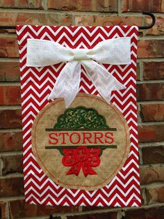 This garden flag is approximately 12 x 18 inches and made out of duck cloth fabric and burlap. Please include the name to be embroidered when ordering. Christmas Garden Flag, Christmas Ideas, Flag Wreath, Yard Flags, Outdoor Flags, Making Out, Burlap, Wreaths, Door Hangers