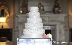 Four tier cake adorned with daisies with sparkling centres simply finished with small posy of flowers