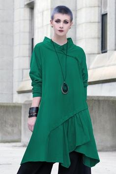 This mid-length coat features a full stand-up collar with hood, sculpted oversized pockets, and front button closure. Cut to give you room for extra layers, and