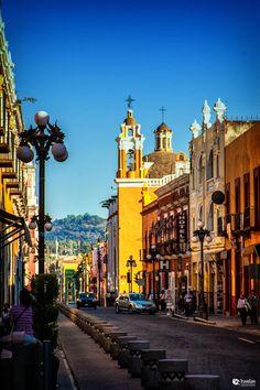 Este foto es de los calles de Puebla. La acera sigue derecho entre de los edificios. Los edificios son altos y el árbol es como alto que los edificios.