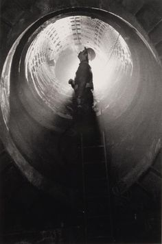 by Sebastiao Salgado - Workers perfect silhouette in the middle of the circle, eye is drawn, detail still in figure. minimalist