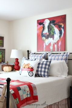 Whimsical Fall in the Guest Room with colorful bedding, vintage quilt, pumpkins, apples, a cute pillow and a psychedelic cow.