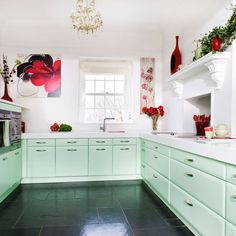I love this green hue and the red decor accents it well. The gold light fixture is adorable but maybe a bit small for a kitchen.