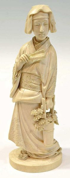 """Description: Japanese ivory carving of a Geisha holding a basket of flowers and fan, excellent detail on the kimono incised with cranes, flowers and waves, signed underfoot as pictured, 8""""h"""