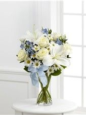 Sweet Peace Bouquet comes with 5 White Roses, 3 Light Blue Delphinium Stems, 3 White Daisy Pompon Stems, 1 White Oriental Lily Stems, 4 Israeli Ruscus Stems and 3 Salal Stems arranged in a Slender Gathering Vase with Light Blue Organza Ribbon.