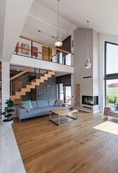 Wysoki salon zaaranżowano w nowoczesnym stylu, ocieplając go zastosowanym drewnem oraz kominkiem. Antresola wzmacnia wrażenie niezwykłej przestrzeni i jednocześnie dodaje wnętrzu lekkości.